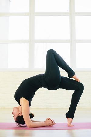 ushtrasana: Beautiful yoga woman practice in a training hall background. Yoga concept. Stock Photo