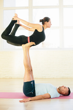 Atractive yoga couple , man and woman, practice exercises in a training hall background. Yoga concept.