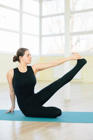 sukhasana: Beautiful yoga woman practice in a training hall background. Yoga concept. Stock Photo