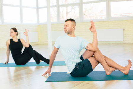 ardha: Atractive yoga couple , man and woman, practice exercises in a training hall background. Yoga concept.