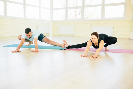 hasta: Atractive yoga couple , man and woman, practice exercises in a training hall background. Yoga concept.