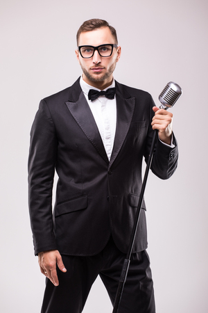 the showman: Front-man in suit singing with the microphone and smile. Isolated on white background. Showman concept. Stock Photo