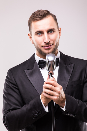 the showman: man in suit singing with the microphone and smile. Isolated on white background. Showman concept.