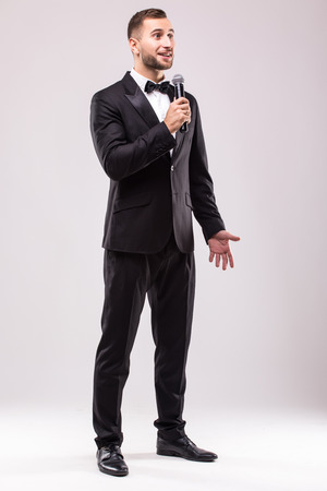 the showman: Young Showman presenter with microphone against white background.Showman concept.