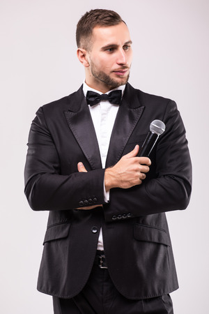 the showman: The Showman interviewer. Young elegant man against white background.Showman concept. Stock Photo