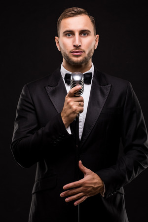 the showman: Handsome Man in suit singing with the microphone and smile. Isolated on black background. Showman concept.