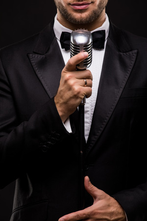the showman: Close-up Handsome Man in suit singing with the microphone and smile. Isolated on black background. Showman concept. Stock Photo