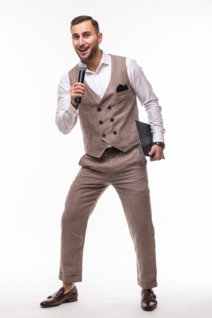 Young man in suit singing over the microphone with energy. Isolated on white background. Singer concept. Stock Photo