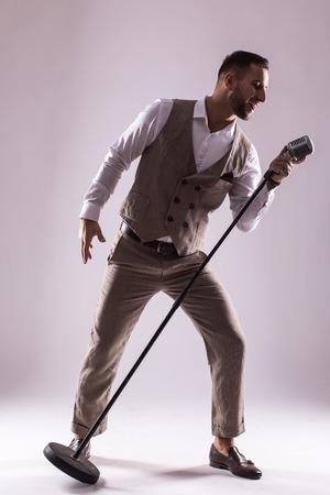 Silhouette del cantante con il microfono su sfondo grigio. concetto di Singer. Archivio Fotografico