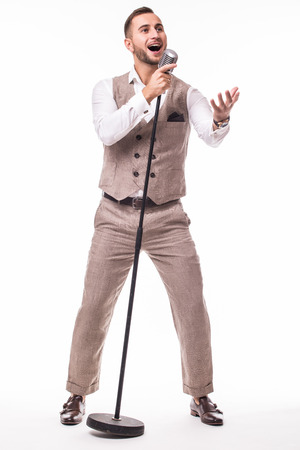Young showman in suit singing with emotions and pointed  gesture over the microphone with energy. Isolated on white background. Singer concept.