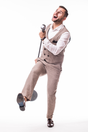 Young showman in suit dance and singing with emotions gesture over the microphone with energy. Isolated on white background. Singer concept.