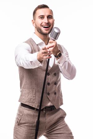 the showman: Portrait young showman in suit singing with emotions gesture over the microphone with energy. Isolated on white background. Singer concept.