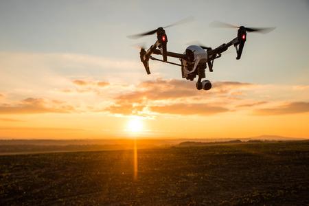 Witte hommel met digitale camera vliegen in de hemel over veld op zonsondergang Stockfoto - 65651444