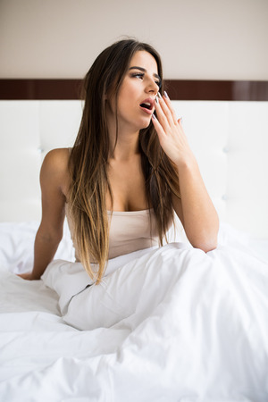 Sleepy young woman yawning in bed at home