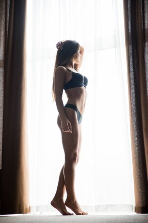 sexy woman standing: Sihluette of sexy woman standing near window Stock Photo