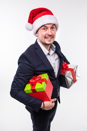 Happy handsome business man in christmas hat with gifts box in hands over white backgrounds Stock Photo