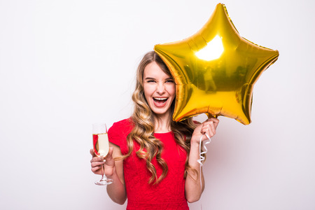 Pretty young woman in red dress with gold star shaped balloon smiling and drinking champagne over white background