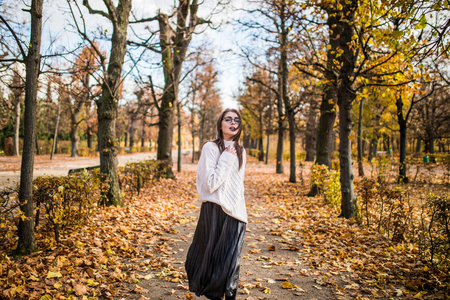 arhitecture: Young girl walking in windy autumn park Stock Photo