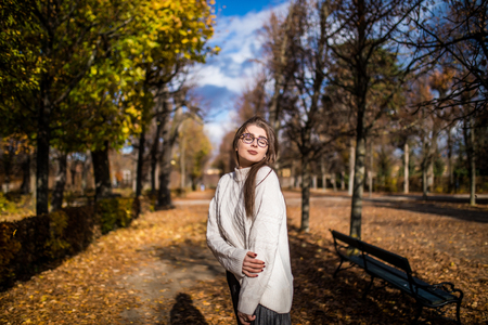 Young girl walking in windy autumn park over blue sky