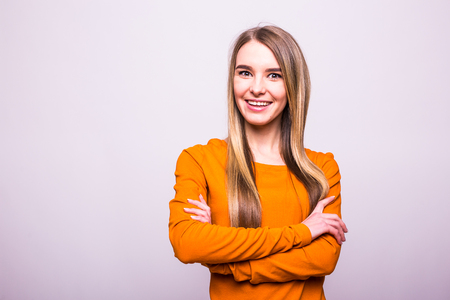 Happy blonde girl in orange t-shirt with crossed hands on white Stock Photo