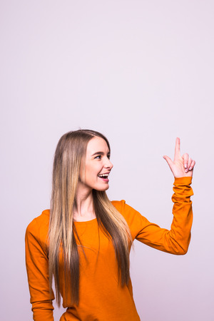 Happy blonde girl in orange t-shirt pointed up on white