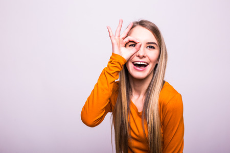 Happy blonde girl with okay gesture on white Stock Photo