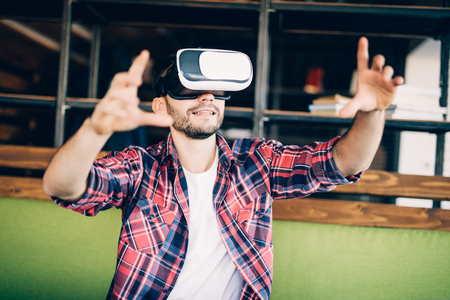 Bearded young man wearing virtual reality goggles in modern coworking studio. Stock Photo