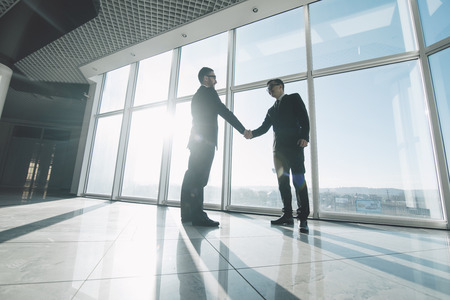 Two young businessmen are shaking hands with each other standing against panoramic windows. Foto de archivo