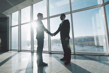 パノラマの窓に対しての握手ビジネスマンの全長側面図 写真素材