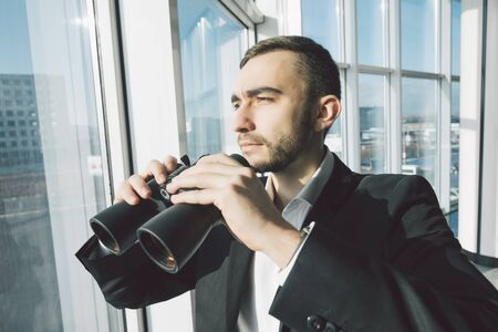 using binoculars: american businessman using binoculars in office