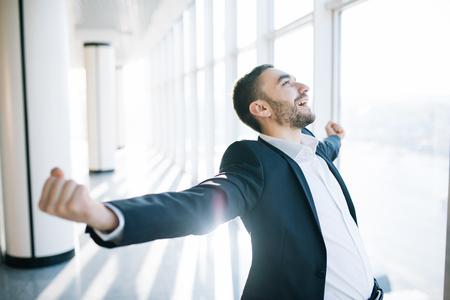 Increíble alegría de hombre de negocios. Gerente feliz al lado de la ventana de la oficina. Piensa en el premio gordo. Foto de archivo