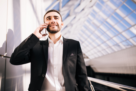 profesional: Young businessman speak on phone and walking around office