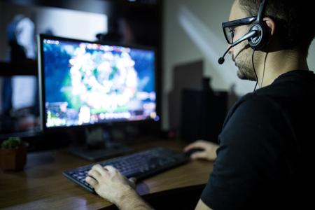夜のプレイ。若いゲーマーにヘッドフォンとメガネを再生するためのコンピューターを使用してゲームの家で