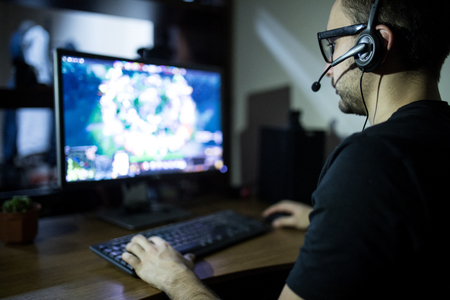night play. young gamer in headphones and glasses using computer for playing game at home Archivio Fotografico