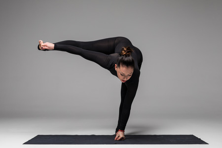 Beautiful yoga woman practice yoga poses on grey background. Yoga concept.