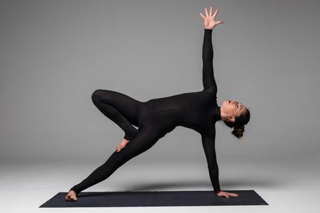 Vasishthasana. Beautiful yoga woman practice yoga poses on grey background. Yoga concept.