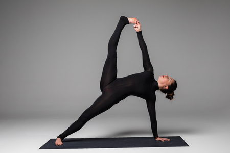 Vasishthasana. Beautiful yoga woman practice yoga poses on grey background. Yoga concept.