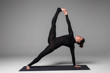 hasta: Vasishthasana. Beautiful yoga woman practice yoga poses on grey background. Yoga concept.