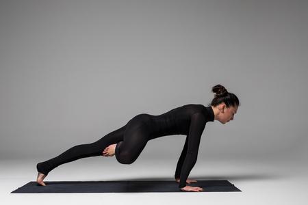Ardha shirshasana. Beautiful yoga woman practice yoga poses on grey background. Yoga concept.