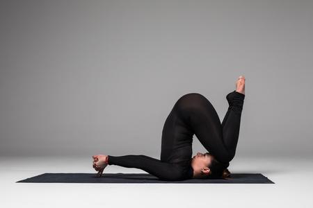 sukhasana: Beautiful yoga woman practice yoga poses on grey background. Yoga concept.