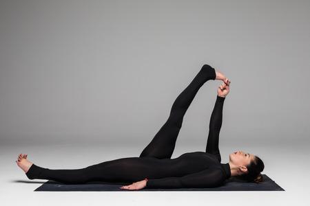 ushtrasana: Beautiful yoga woman practice yoga poses on grey background. Yoga concept.