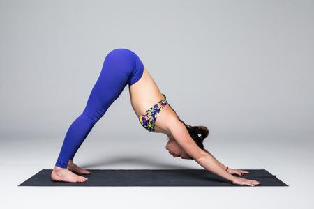 ushtrasana: Adho mukha svanasana. Beautiful yoga woman practice yoga poses on grey background. Yoga concept.