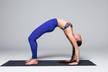 Bridge. Beautiful yoga woman practice yoga poses on grey background. Yoga concept. Stock Photo