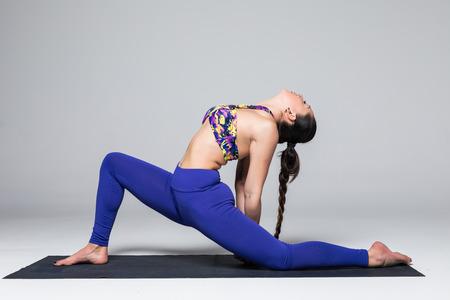 Anjanejasana.  Beautiful yoga woman practice yoga poses on grey background. Yoga concept.