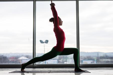 ushtrasana: Anjaneyasana. Beautiful yoga woman practice crescent lunge poses in a big window hall background. Yoga concept. Stock Photo