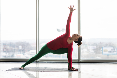 Utthita parsvakonasana. Beautiful yoga woman practice twist poses in a big window hall background. Yoga concept.
