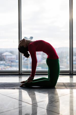 ushtrasana: Ushtrasana. Beautiful yoga woman practice in a big window hall background. Yoga concept. Stock Photo