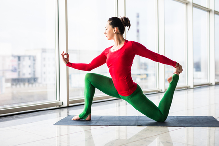 shirshasana: Beautiful yoga woman practice in a big window hall background. Yoga concept.