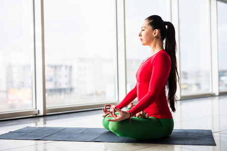 hasta: Guptasana. Beautiful yoga woman practice in a big window hall background. Yoga concept.
