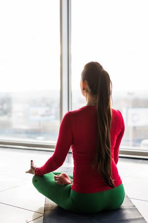 Guptasana. Beautiful yoga woman practice in a big window hall background. Yoga concept.